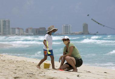 туристы в масках на пляже 2020