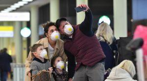 туристы в аэропорту во время коронавируса
